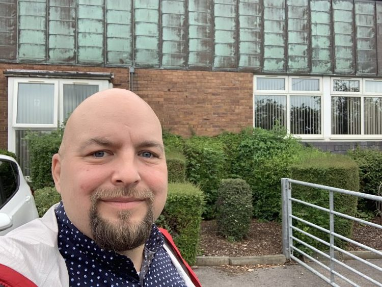 This picture shows Adam Fletcher standing outside a school in Preston, Lancashire, in the UK.
